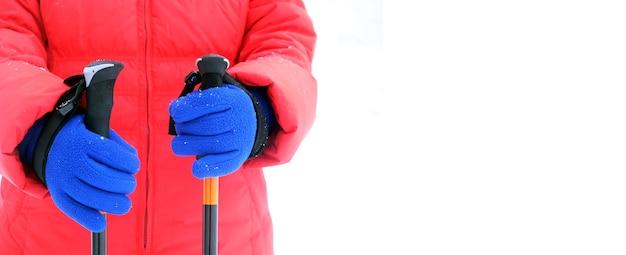 Humano em uma jaqueta esportiva vermelha e luvas azuis segura duas varas para caminhadas no inverno, isoladas no fundo branco, com espaço livre para texto no lado direito da foto