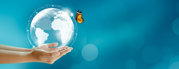 Humano segurando a terra e a borboleta sobre o fundo verde borrão meio ambiente mundial e conceito verde