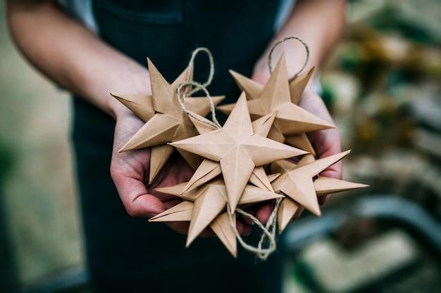 Humano segurando estrelas de papel kraft feito à mão nas mãos