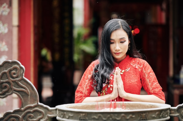 Humilde, jovem e bonita mulher vietnamita rezando em um templo budista ao lado de uma urna de bronze queimando incensos