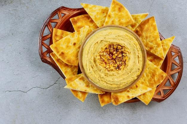 Hummus árabe no pão da bacia e do pão árabe na tabela branca.