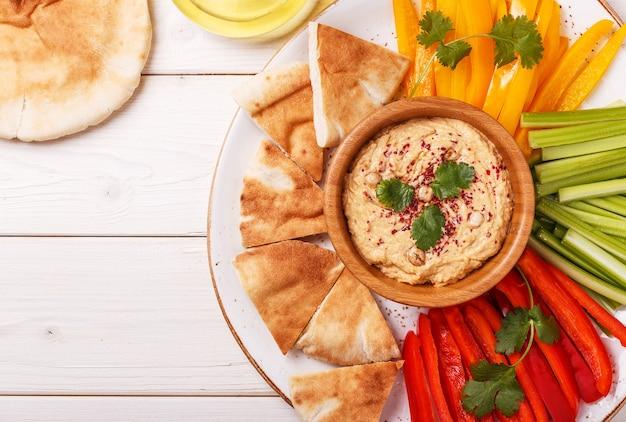 Hummus caseiro saudável com legumes frescos variados e pão pita.