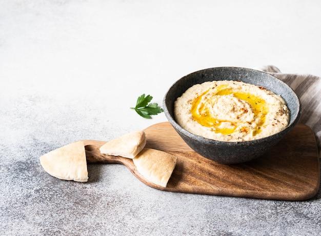 Hummus caseiro tradicional de ervilha de pintainho na tigela, regados com azeite e tempero de páprica seca na tábua de madeira.