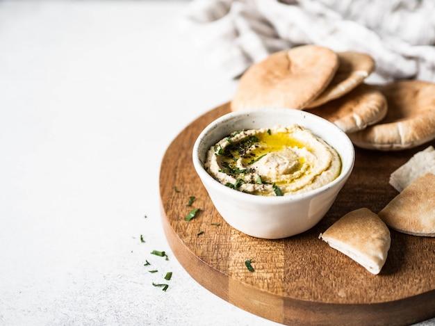 Hummus caseiro tradicional de ervilha de pintainho, regados com azeite de oliva, salsa fresca e fatias de pão árabe fresco na tábua de madeira. copie o espaço