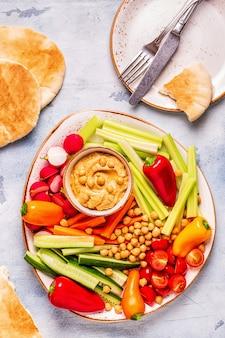 Hummus com vários vegetais crus frescos