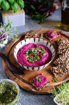 Hummus de beterraba assada na tigela de cerâmica, biscoitos de semente de linho na tábua de madeira