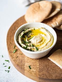 Hummus de ervilha de grão de bico caseiro tradicional, regado com azeite de oliva e salsa fresca e fatias de pita frescas na tábua de madeira