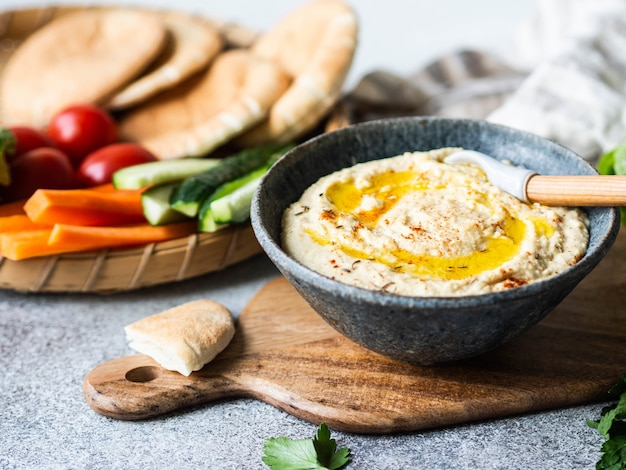 Hummus de propagação caseiro caseiro, servido com legumes frescos, pão árabe e ervas na bandeja