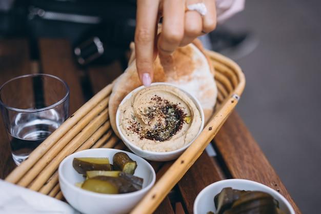 Hummus delicioso fresco, pão pita e pepinos em conserva