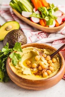 Hummus do abacate em uma bacia de madeira com vegetais.