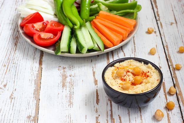 Hummus em tigela, palitos de legumes, grão de bico, azeitonas.