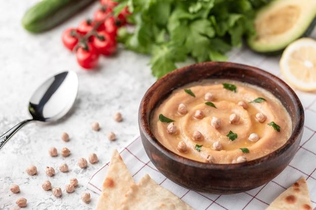 Hummus em uma placa de madeira marrom. na mesa branca estão legumes, verduras, pedaços triangulares de pão árabe.