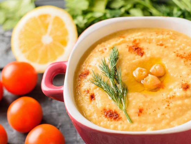 Hummus fresco em uma tigela roxa e limão em uma mesa com um pedaço de pão