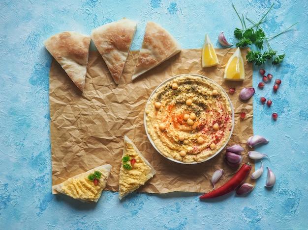 Hummus tradicional e pellet de pão quebrado em pergaminho.
