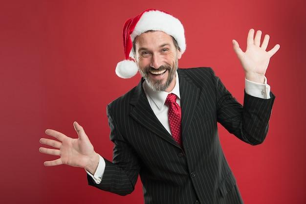 Humor alegre. começar um negócio que gira em torno da época do natal. negócios e corporativos. conceito de festa de natal. homem com barba em terno inteligente e chapéu de papai noel. empresário comemora o natal.