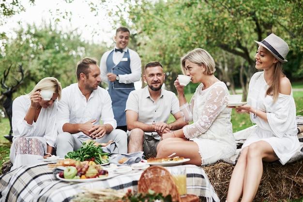 Humor alegre. grupo de amigos adultos descansam e conversam no quintal do restaurante na hora do jantar.