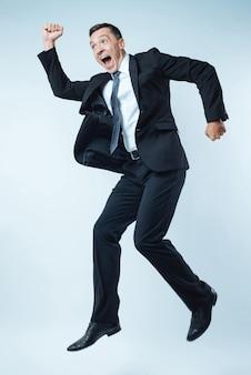 Humor alegre. homem bonito emocional encantado rindo e pulando de felicidade ao mesmo tempo em que está muito animado