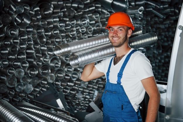 Humor alegre. homem de uniforme trabalha na produção. tecnologia industrial moderna.