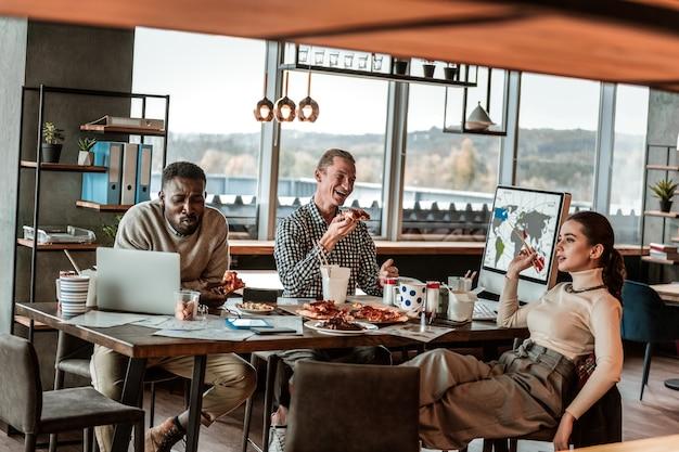 Humor alegre. homem emocional de pele escura inclinado sobre a mesa enquanto comia pizza com os colegas