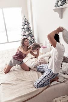 Humor alegre. jovem bonito e barbudo e sua esposa usando meias brancas grossas se sentindo bem