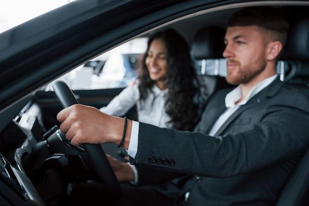 Humor alegre. lindo casal de sucesso experimentando um carro novo no salão de automóveis