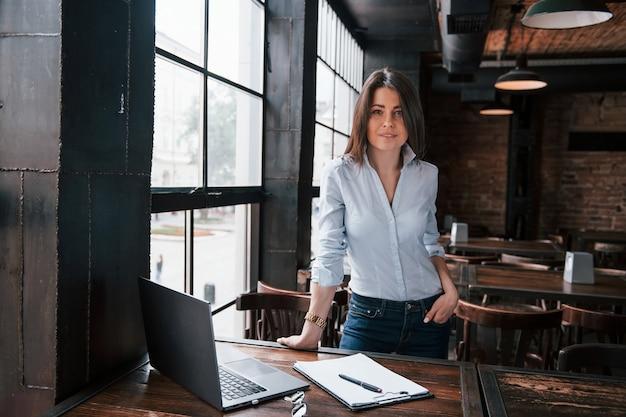 Humor alegre. mulher de negócios com roupas oficiais está dentro de casa no café durante o dia.