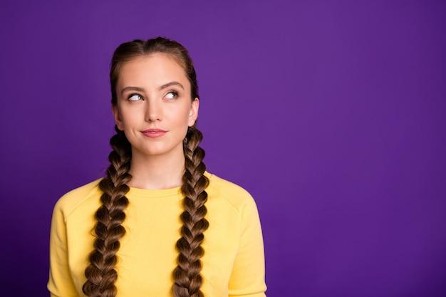 Humor complicado senhora tranças compridas penteado procurando astuto espaço vazio tem uma ideia maluca usar pulôver amarelo casual isolado parede cor roxa