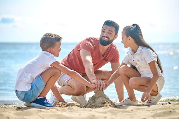 Humor criativo. um pai com crianças fazendo castelos de areia
