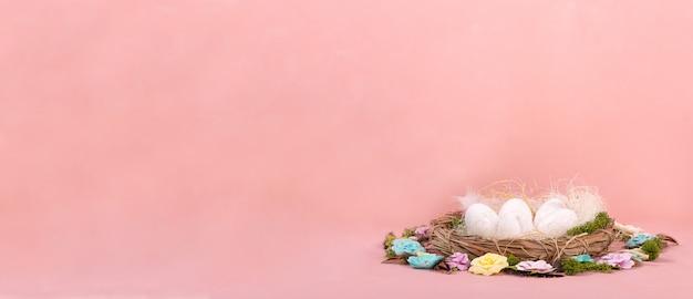 Humor da mola, decoração de easter dos ovos, flores de papel, uma grinalda das videiras em um fundo coral vivo.