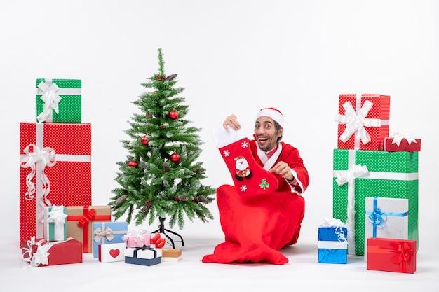 Humor de ano novo com o papai noel sorridente sentado no chão e usando uma meia de natal perto de presentes e uma árvore de natal decorada em fundo branco