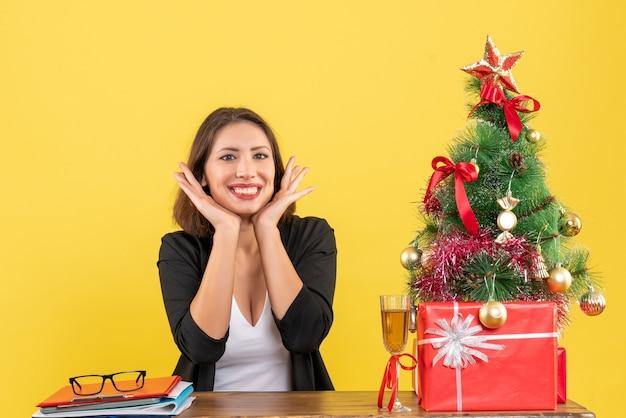 Humor de ano novo com uma linda mulher de negócios feliz e satisfeita sentada a uma mesa no escritório