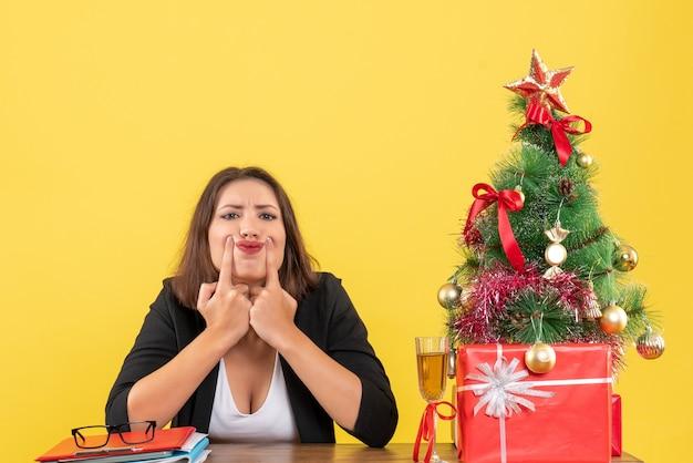 Humor de ano novo com uma linda senhora de negócios nervosa e insatisfeita, confusa com alguma coisa e sentada à mesa do escritório
