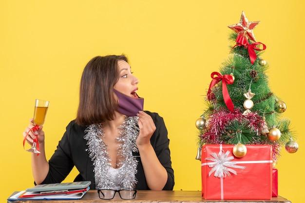 Humor de natal com bela dama de terno abrindo máscara médica e levantando vinho no escritório em amarelo