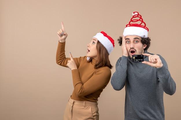 Humor de natal com casal legal animado usando chapéus vermelhos de papai noel chateado cara mostrando o cartão do banco. mulher apontando para cima