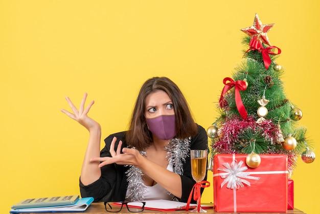 Humor de natal com confusa senhora encantadora de terno usando máscara médica no escritório em amarelo isolado