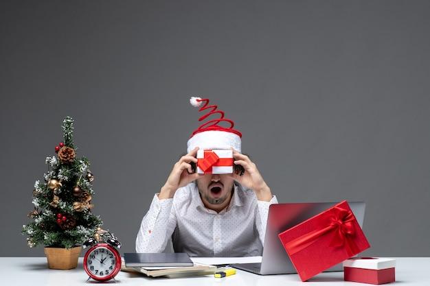 Humor de natal com empresário engraçado com chapéu de papai noel segurando seu presente na frente do rosto em fundo escuro