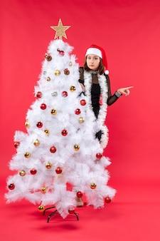 Humor de natal com garota linda e surpresa em um vestido preto com chapéu de papai noel se escondendo atrás da árvore de ano novo