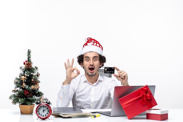 Humor de natal com jovem barbudo chocado empresário orgulhoso com chapéu de papai noel segurando o cartão do banco, fazendo gesto de óculos no fundo branco