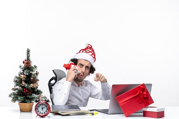 Humor de natal com jovem barbudo empresário chocado com chapéu de papai noel levantando seu presente e apontando algo em fundo escuro