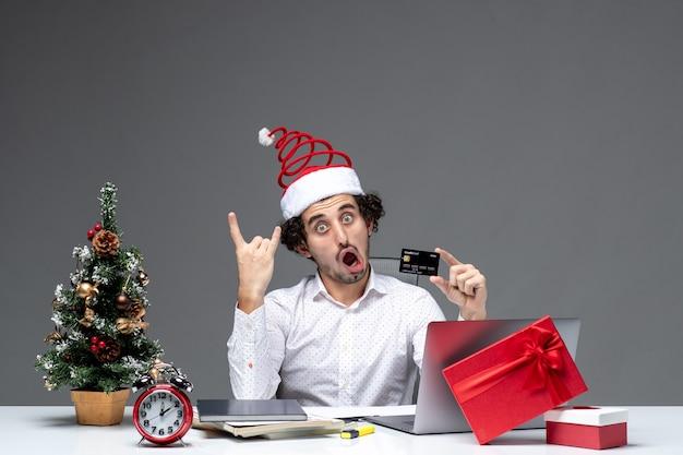 Humor de natal com jovem barbudo empresário chocado engraçado com chapéu de papai noel segurando um cartão do banco e mostrando dois em fundo escuro