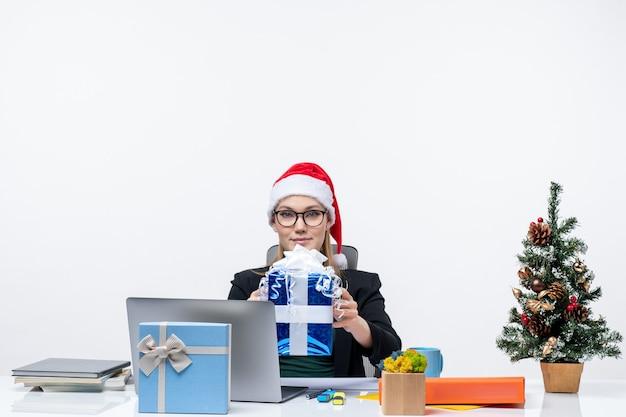 Humor de natal com jovem com chapéu de papai noel e usando óculos, sentado em uma mesa mostrando um presente no fundo branco