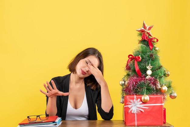 Humor de natal com jovem sério concentrado mulher bonita sentada no escritório em amarelo