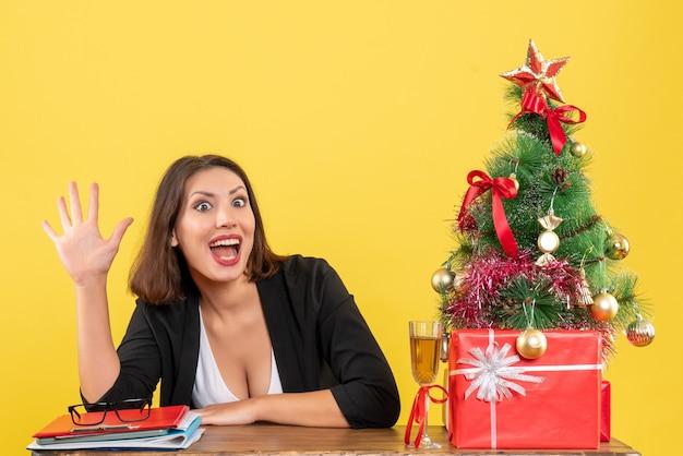 Humor de natal com jovem sorridente e satisfeita mostrando cinco em amarelo