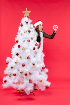 Humor de natal com linda jovem surpresa em um vestido preto com chapéu de papai noel se escondendo atrás da árvore do ano novo