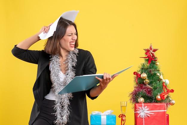 Humor de natal com linda senhora emocional em pé no escritório investigando documentos em amarelo