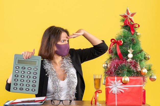 Humor de natal com mulher bonita concentrada de terno usando máscara médica segurando calculadora focada em algo no escritório em amarelo