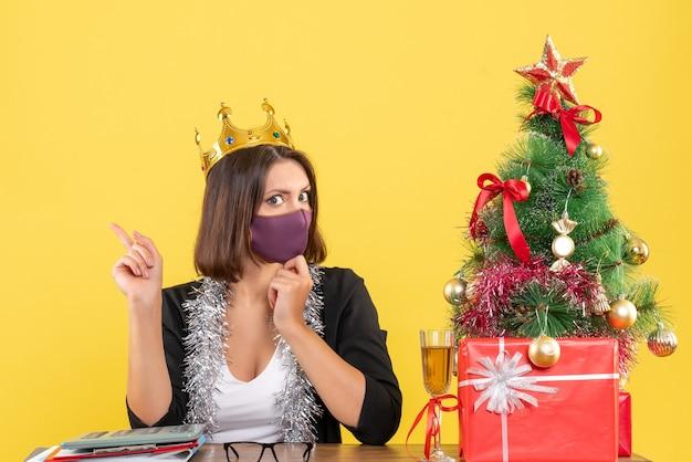 Humor de natal com mulher bonita concentrada em um terno com coroa usando sua máscara médica no escritório em amarelo