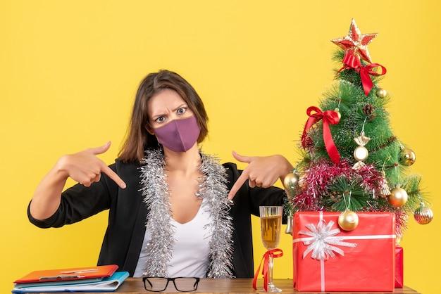 Humor de natal com senhora encantadora de terno usando máscara médica apontando para baixo no escritório em amarelo isolado