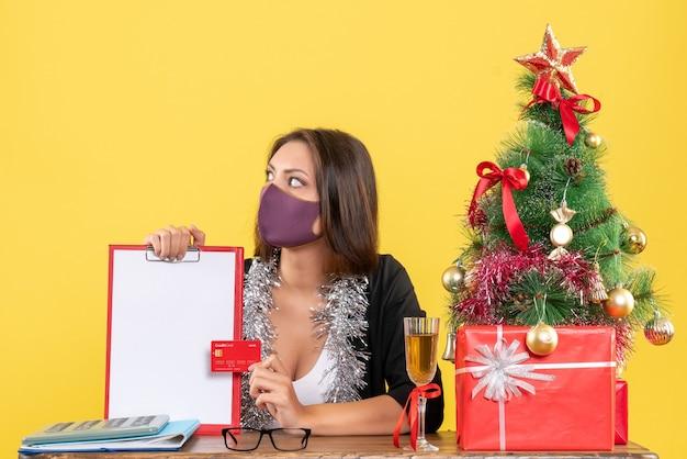 Humor de natal com senhora encantadora de terno usando máscara médica, segurando o documento e o cartão do banco no escritório em amarelo isolado