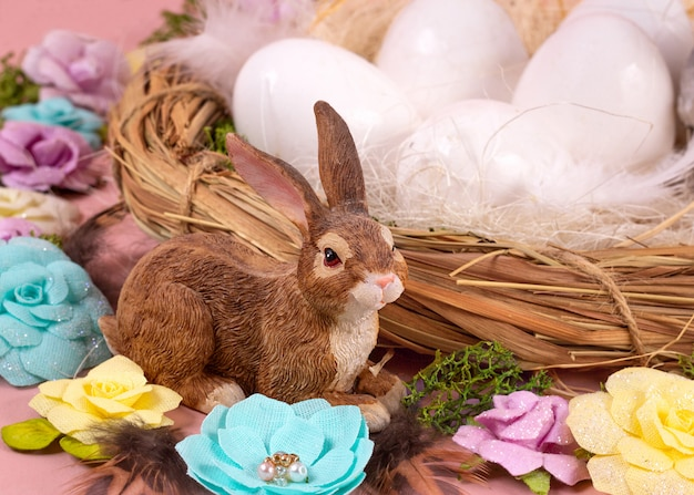 Humor de primavera, decoração de páscoa de ovos, flores de papel, uma coroa de videiras e coelhos bonitos pequenos sobre um fundo de coral vivo. faixa larga - imagem.